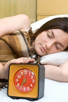 Young woman hitting the snooze button